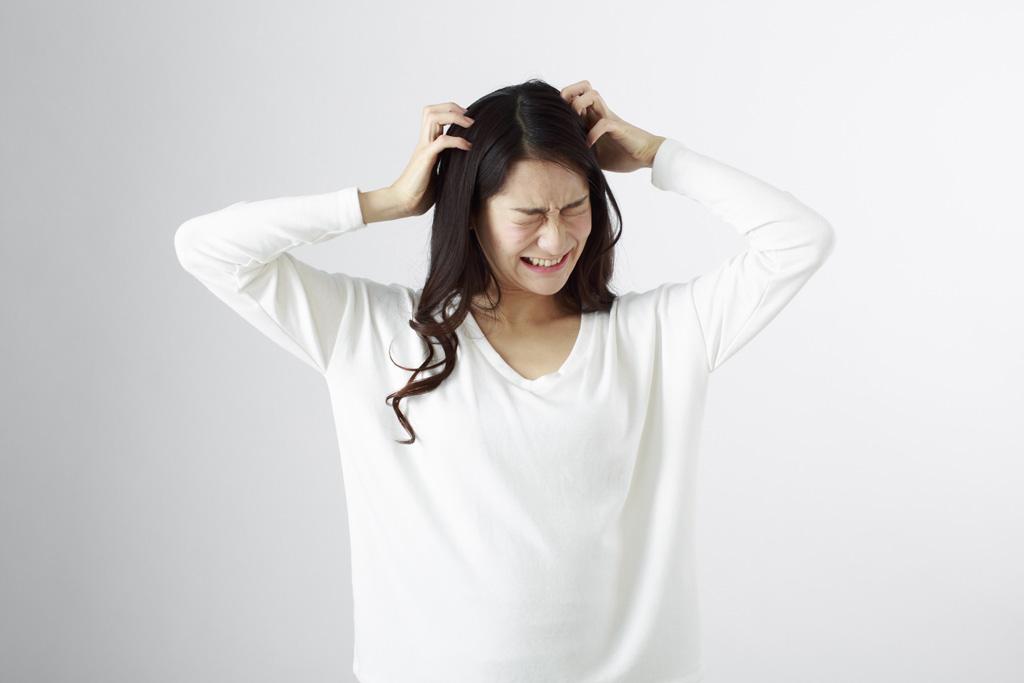 イライラして頭を掻く女性