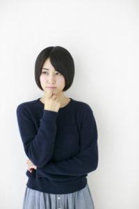 顎に手を当てて考える日本人女性
