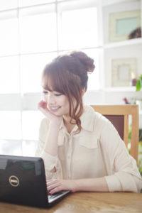 ミニノートパソコンを見て楽しむ女性