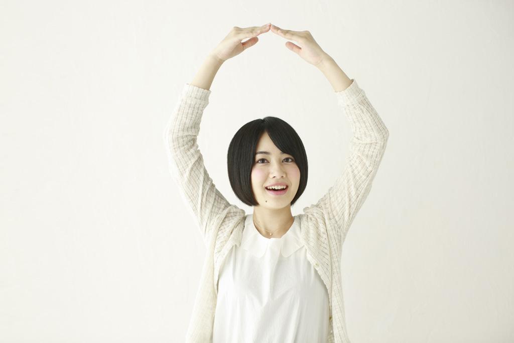 頭の上でマルを作る日本人女性