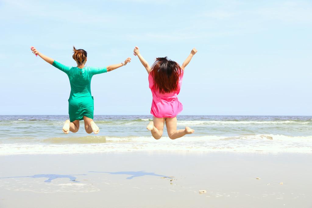 波打ち際で歓喜する二人の女性
