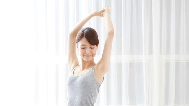 手を伸ばして背伸びする女性